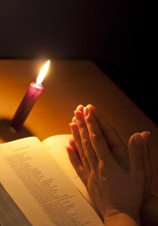 manos orando: Oración de la Biblia y la vela en la noche concepto de la meditación Foto de archivo