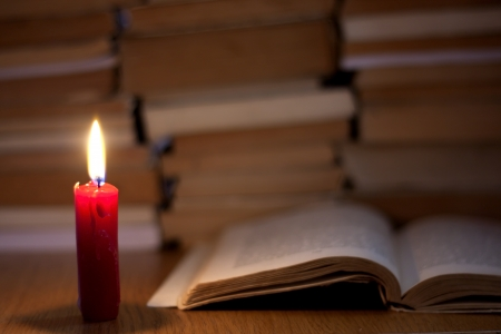 old books and candle light abstract background photo