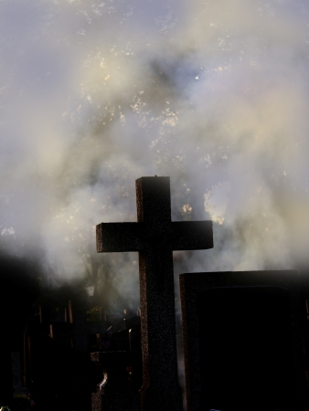 cross and smoke at cemetery photo