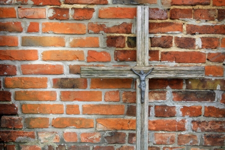 Jesus Christ on wooden cross against brick wall photo