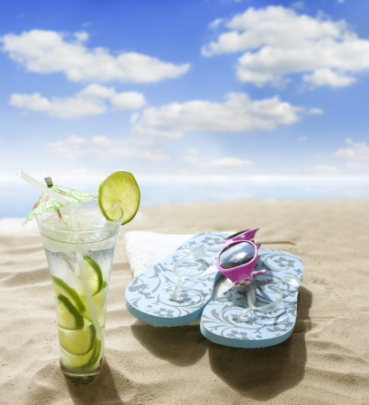 sunglasses drink in sand on beach at sea holiday concept photo