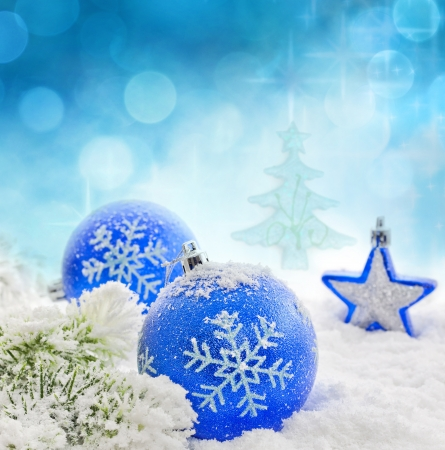 Christmas branch of tree blue baubles and snow background photo