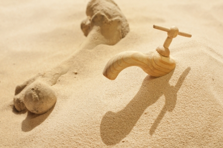 anomalies: Global warming climate change faucet in the sand concept