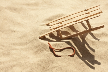 malcontent: bad holiday and sled on the beach metaphor concept Stock Photo