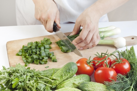Cook in the kitchen at work preparing vegetable salad photo