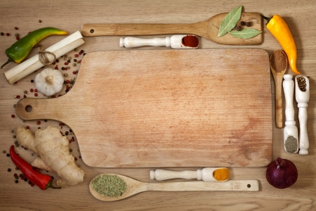 organic background:  vegetables and spices border and empty cutting board