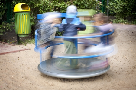 marry go round:  Carousel in motion and happy kids on playground Stock Photo