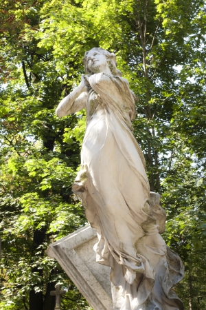 headstones:  Statue of ancient angel on cemetery in Warsaw