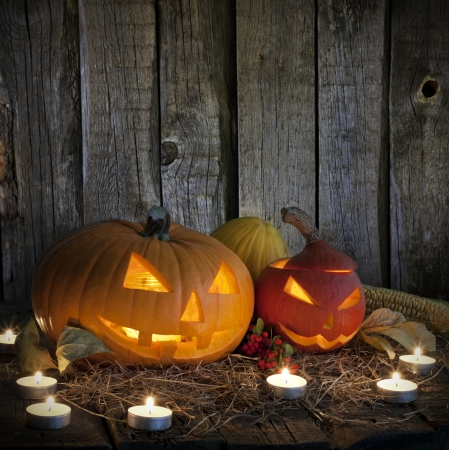 Halloween pumpkins on old grunge boards and candles photo