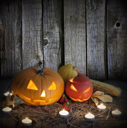 carved pumpkin:  Halloween pumpkins on old grunge boards and candles Stock Photo