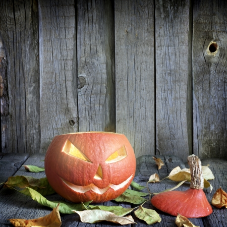carved pumpkin:  Halloween pumpkins on old grunge boards with leaves background Stock Photo