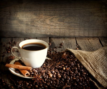 Cup of coffee with beans and cinnamon vintage still life photo