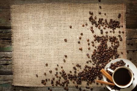 Cup of coffee with beans and cinnamon vintage background photo
