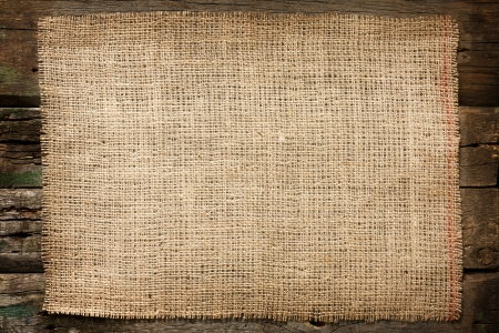 Burlap jute canvas vintage background on wooden boards photo