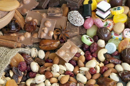 Chocolate nuts dried fruits and candy background photo