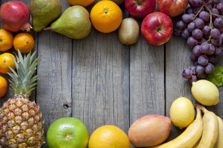 Fresh fruits on wooden boards frame background photo