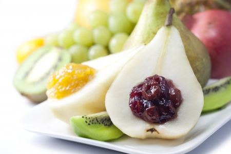 Fruits and pears with jam closeup luxury food concept on white photo