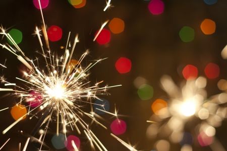 bang: Sparkler and colorful bokeh christmas new year background  Stock Photo