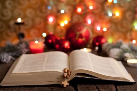 biblia: Navidad y la biblia con el fondo borroso de luz velas