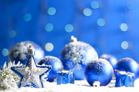 christmas embellishments: Christmas star closeup and baubles on blue blurred background Stock Photo