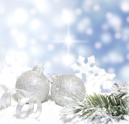 christmas concept: Christmas branch of tree ribbon silver baubles and snow on blue background Stock Photo