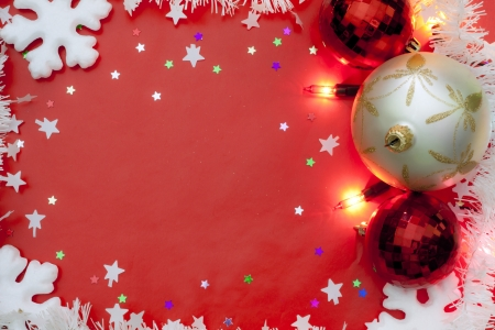 Christmas lights border with baubles and snow on red background