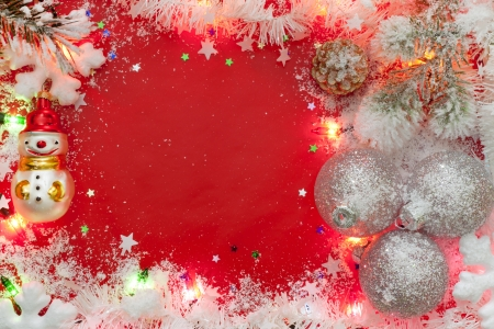 Christmas lights border with baubles and snow on red background photo