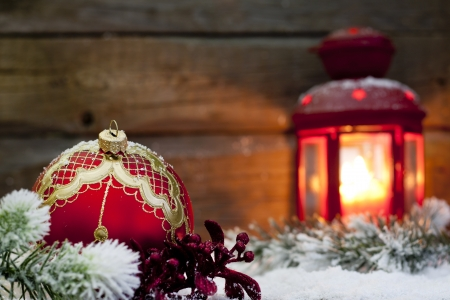 Christmas red bauble and lantern in night on snow with fir