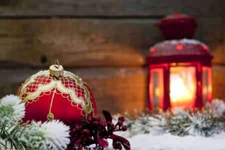 velas de navidad: Navidad chuchería roja y una linterna en la noche en la nieve con el abeto