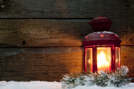 advent: Christmas lantern light in night on snow and wooden boards