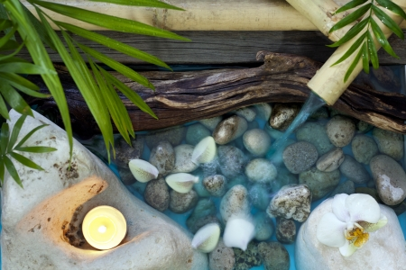 Falling water on stones spa concept background with orchids and bamboo