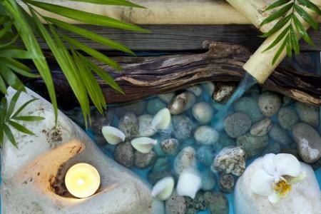 Vallende water op stenen spa concept achtergrond met orchideeën en bamboe