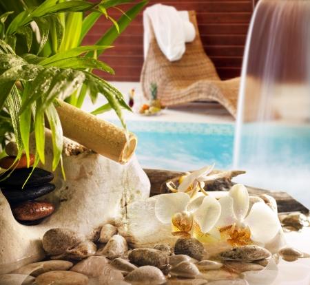 Spa concept met stenen orchideeën waterval in het zwembad en zonnebank Stockfoto