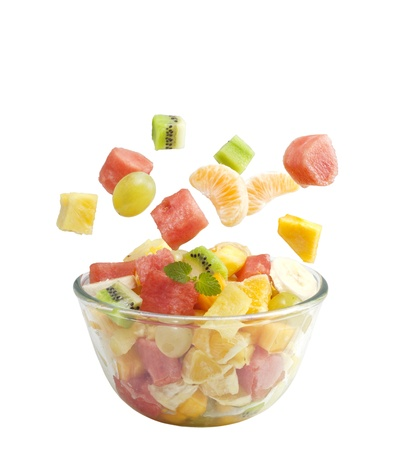 Fruits salad flies to the bowl isolated on white background photo