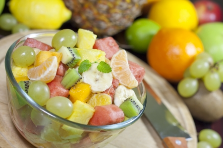 Fresh fruits salad in bowl in kitchen closeup photo
