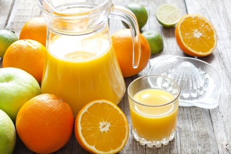 juice squeezer: Orange juice with lime grapefruit and squeezer on wooden boards Stock Photo