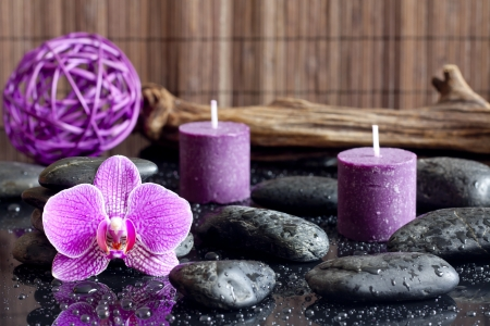 retreat: Purple orchid candles and zen stones spa concept still life