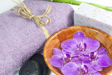 Orchids in the bowl with towel spa cosmetic concept photo