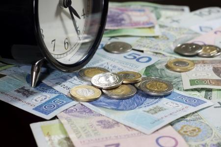 Tijd is geld concept met polish munten en bankbiljetten