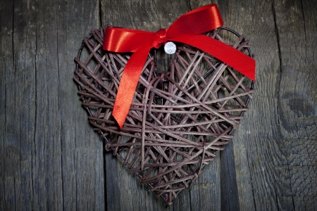 Wicker heart on wooden boards valentines concept photo