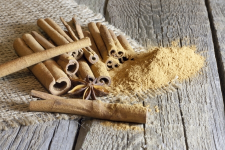 Cinnamon sticks and meal on wooden boards Stock Photo - 17459074