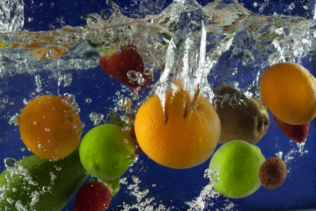 Fruits splash in water with bubbles against blue background photo