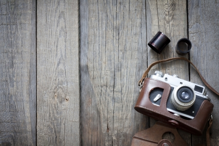 old camera: Old retro camera on vintage wooden boards abstract background