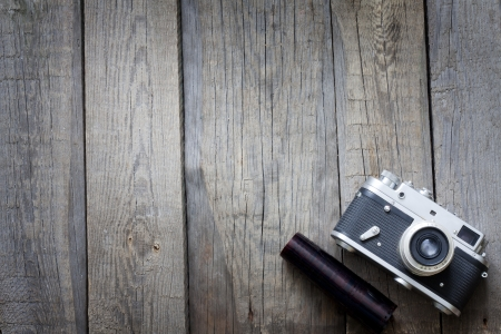 studio photography: Old retro camera on vintage wooden boards abstract background