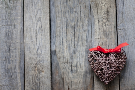 cute love: Wicker heart on vintage boards love background concept