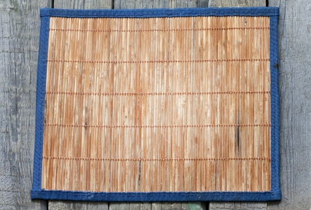 Bamboo mat on vintage wooden boards food background concept photo