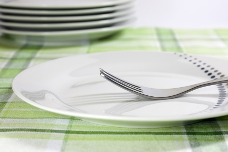 starvation: Plates on tablecloth in kitchen abstract food background