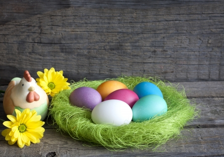 spring time: Easter eggs in green nest on vintage wooden planks