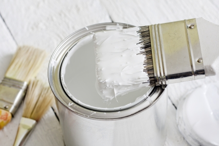 Paint brush and can on white planks photo
