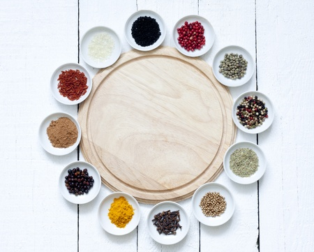 Spices and dried vegetables with cutting board on white planks 免版税图像